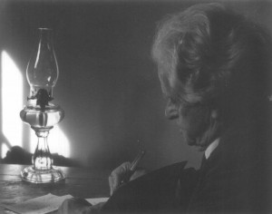 John Neihardt writing in study with lamp